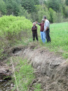 Kim Komer (Lamoille Natural Resource Conservation District), Roy Schoolcraft (landowner) and Steve Libby (VRC Executive Director) examine the banks of the Wild Branch